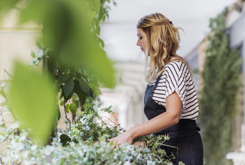 Side view of florist carrying leaves basket