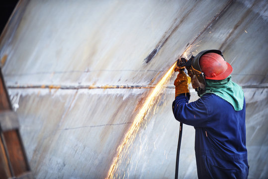 Side view of worker welding ship at industry