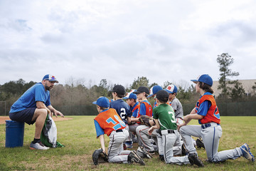 Coach talking to baseball team on field