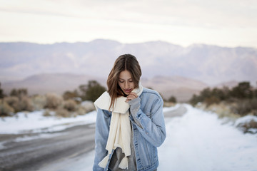 Young woman holding muffler while standing on snow covered road against mountains