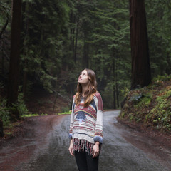 Young woman looking up while standing on road in forest