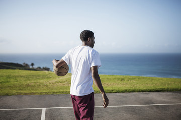 Man with basketball at court by sea against sky