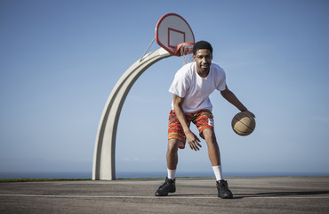 Portrait of man playing with basketball against clear blue sky