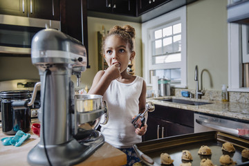 Girl eating while preparing chocolate chip cookies in kitchen