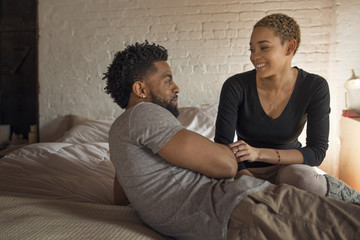 Happy young couple looking at each other in bedroom