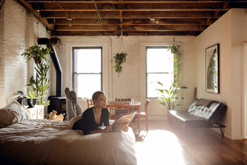 Woman reading newspaper while lying on bed at home