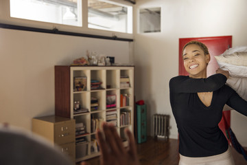 Cheerful young woman throwing pillow on man at home