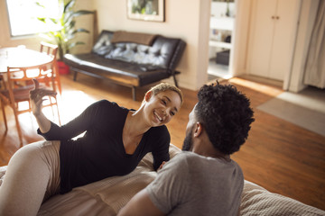 High angle view of happy woman talking to man in bedroom