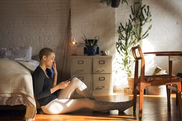 Side view of happy woman using tablet computer while sitting on floor in bedroom