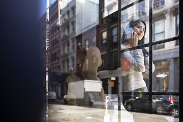 Young woman answering smart phone seen through glass wall