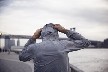 Rear view of male athlete wearing hooded jacket with Williamsburg Bridge in background