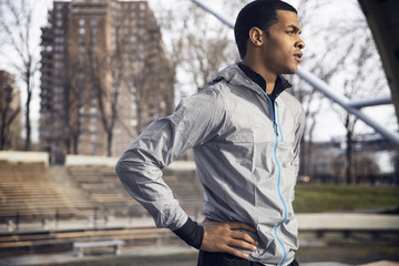 Thoughtful male athlete standing with hand on hip at park