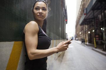 Thoughtful sporty woman holding smart phone while leaning on wall by street