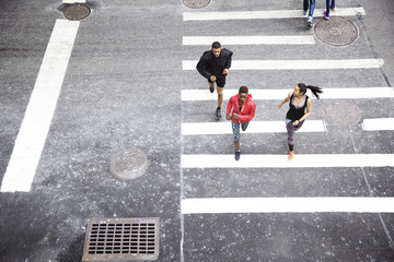Overhead view of athletes running on zebra crossing