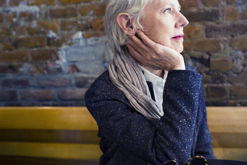 Thoughtful senior woman sitting at sidewalk cafe