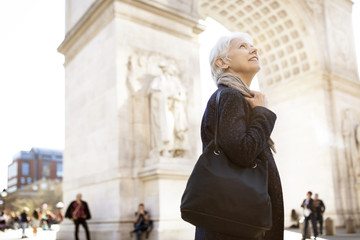 Side view of senior woman looking up while standing against triumphal arch in city