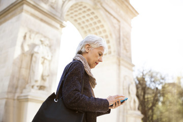 Side view of senior woman using smart phone while standing against triumphal arch in city