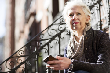 Thoughtful senior woman holding smart phone outdoors