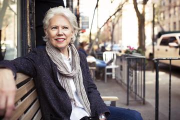 Thoughtful senior woman sitting on bench at sidewalk