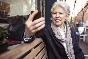 Smiling senior woman using smart phone while sitting on bench