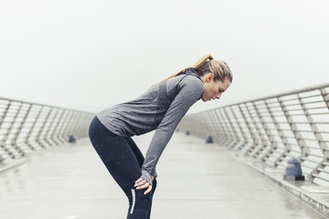Tired female athlete relaxing on bridge against clear sky