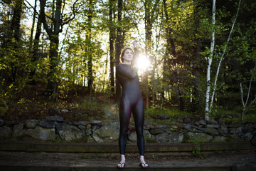 Determined female swimmer stretching arms in forest