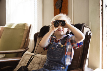 Boy looking through binoculars while sitting on chair at home