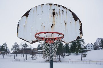 Close-up of rusty basketball hoop on snow covered field