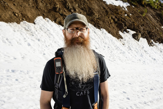 Portrait of confident man standing on snow covered mountain