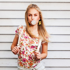 portrait of a beautiful young hipster girl with chewing gum. Blonde girl standing near white wall with backpack