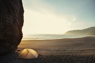 Tent by cliff on beach against clear sky during sunset