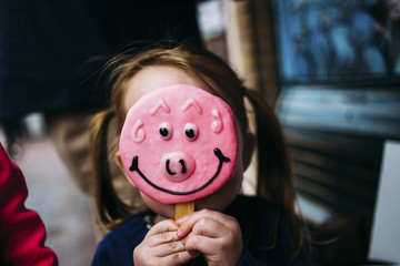 Close-up of girl hiding face with candy