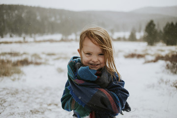 Portrait of happy girl wrapped in blanket during winter