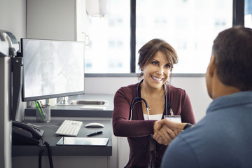 Happy female doctor shaking hands with male patient in clinic