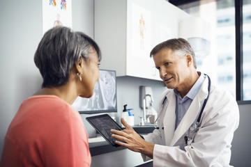 Male doctor explaining x-ray on tablet computer to patient in clinic