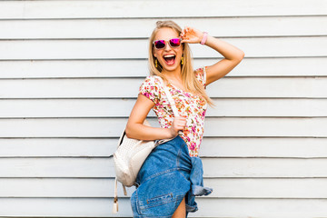 Funny cool cute beautiful hipster blonde girl posing against a white wall, bright casual wear, denim shirt, T-shirt, sunglasses, backpack, urban style, laughs, a broad smile, crazy emotions, joy
