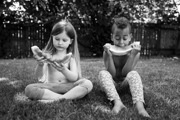 Children eating watermelon slices while sitting on the grass