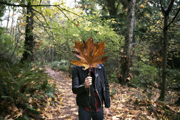Man holding dry maple leaf in front of face at forest during autumn