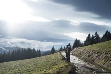 Man and woman standing on mountain against cloudy sky
