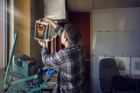 Male lithograph worker hanging prints to dry at workshop