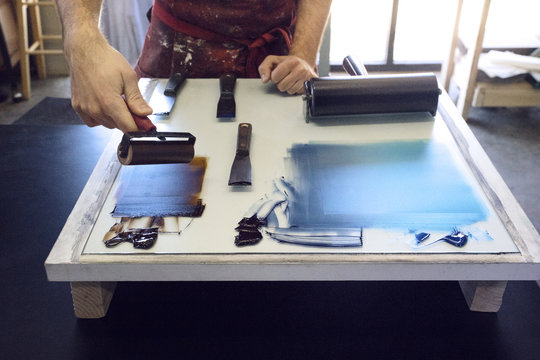 Midsection of lithograph worker using paint roller at workshop
