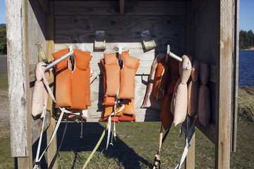 Life jackets hanging in wooden shed by lake