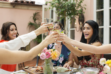 Happy female friends toasting drinks at outdoor restaurant