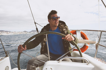 Happy man driving nautical vessel on sea against cloudy sky