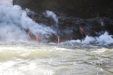 Steam emitting from lava rocks by sea