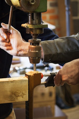 Cropped image of hands using machine to drill wood in workshop