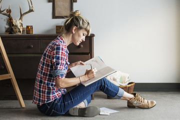 Female artist drawing in book while sitting at home