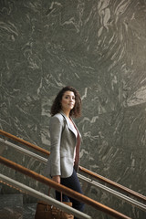 Thoughtful businesswoman standing on steps in modern building