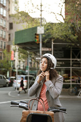 Businesswoman wearing helmet while standing by Citi Bike on street