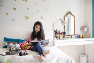 Teenage girl sitting on bed and reading book at home